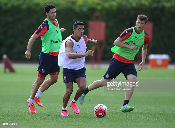 Mikel Arteta Alexis Sanchez and Krystain Bielik of Arsenal during a training session at London Colney on August 8 2015 in St Albans England