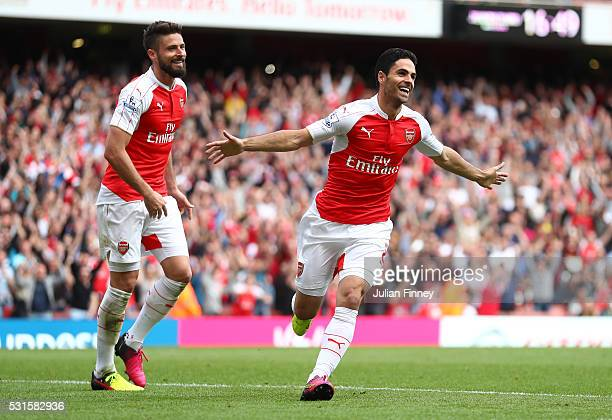 Mikel Arteta and Olivier Giroud of Arsenal celebrate their team's fourth goal scored own goal by Mark Bunn of Aston Villa during the Barclays Premier...