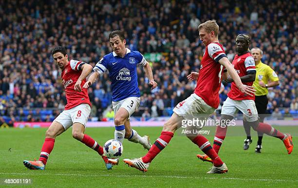 Mikel Arteta and Per Mertesacker of Arsenal competes with Leighton Baines of Everton during the Barclays Premier League match between Everton and...