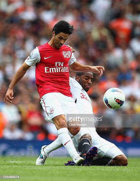 Mikel Arteta if Arsenal is tackled by Kemy Agustien of Swansea City of Swansea City during the Barclays Premier League match between Arsenal and...