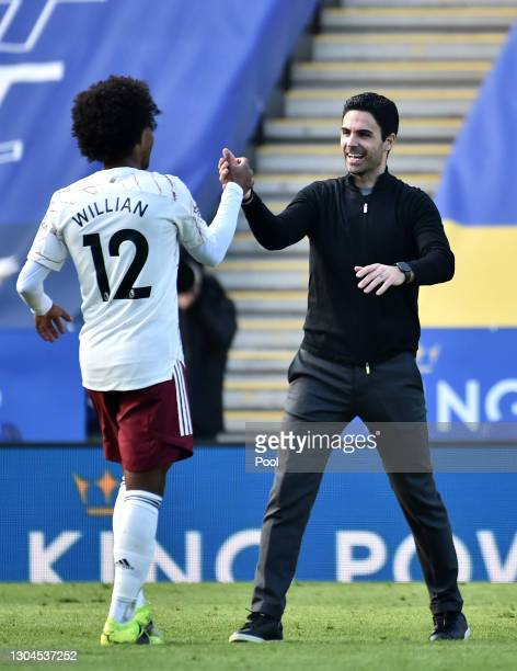 Mikel Arteta, Manager of Arsenal celebrates victory with Willian of Arsenal following the Premier League match between Leicester City and Arsenal at...