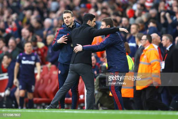 Mikel Arteta Manager of Arsenal embraces his coaching staff following his sides victory in the Premier League match between Arsenal FC and West Ham...