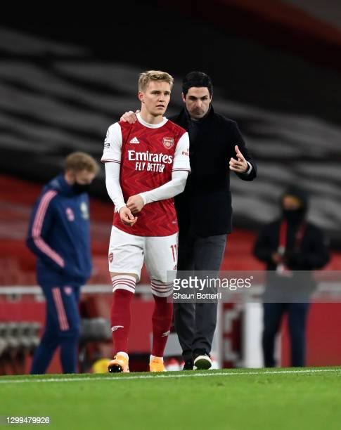 Mikel Arteta, Manager of Arsenal gives Martin Odegaard of Arsenal instructions before coming on for his debut during the Premier League match between...