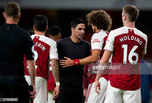 Mikel Arteta Manager of Arsenal speaks with Hector Bellerin David Luiz and Rob Holding of Arsenal following the Premier League match between Arsenal...