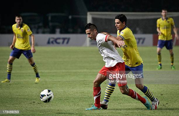 Mikel Arteta of Arsenal battles for the ball with Raphael Maitimo of Indonesia AllStars fight for the ball during the match between Arsenal and the...