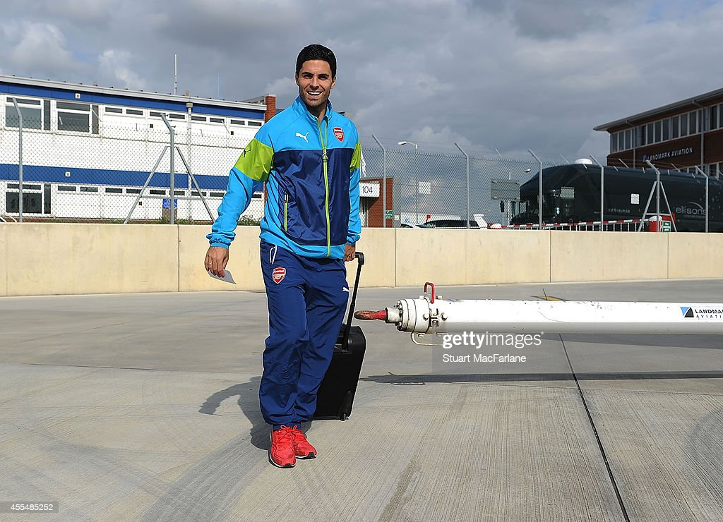 Mikel Arteta of Arsenal boards the team plane at Luton Airport on September 15, 2014 in St Albans, England. Photo by Stuart MacFarlane/Arsenal FC via Getty Images)