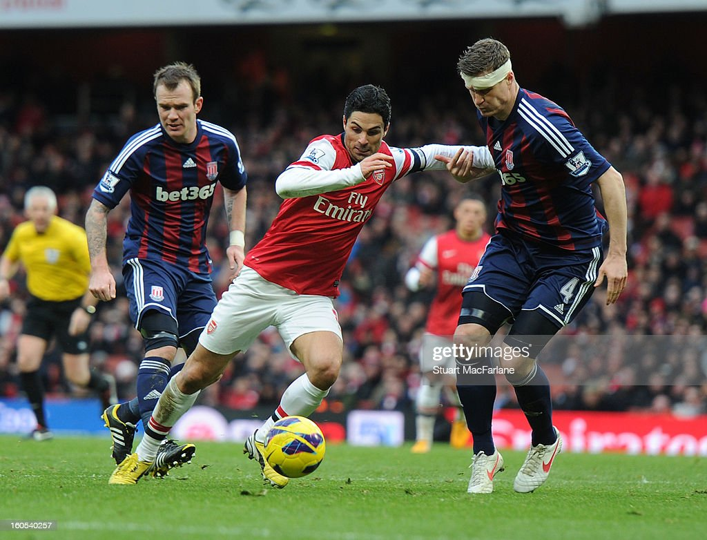 Mikel Arteta of Arsenal challenged by Robert Huth of Stoke during the Barclays Premier League match between Arsenal and Stoke City at Emirates Stadium on February 02, 2013 in London, England.