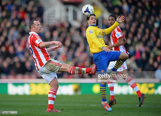 Mikel Arteta of Arsenal competes with Charlie Adam of Stoke City during the Barclays Pemier League match between Stoke City and Arsenal at the...