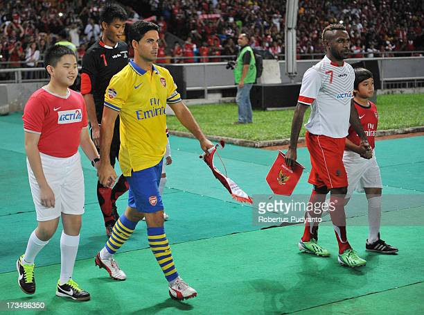 Mikel Arteta of Arsenal FC and Boaz Solossa of Indonesia All Star walk onto the field during the match between Arsenal and the Indonesia AllStars at...