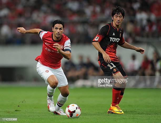 Mikel Arteta of Arsenal FC turns away from Keiji Tamada of Grampus during the pre-season Asian Tour friendly match between Nagoya Grampus and Arsenal...