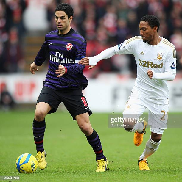 Mikel Arteta of Arsenal holds off Jonathan de Guzman of Swansea City during the FA Cup with Budweiser Third Round match between Swansea City and...