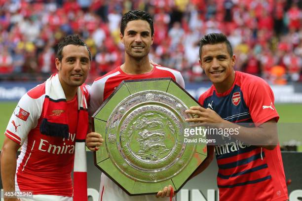 Mikel Arteta of Arsenal holds up the trophy next to Santi Cazorla and Alexis Sanchez after the FA Community Shield match between Manchester City and...