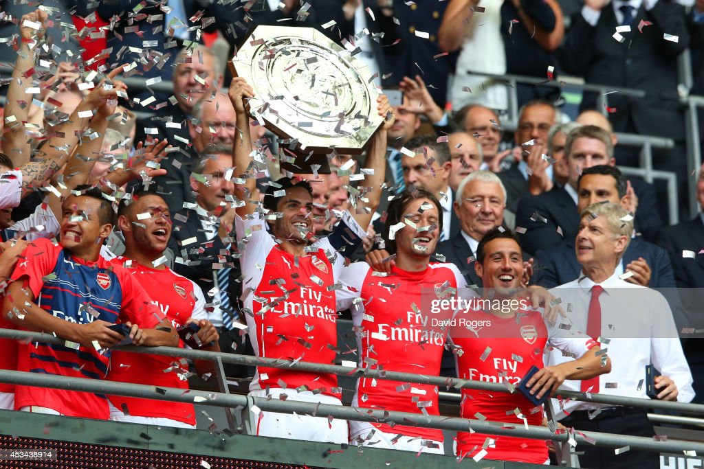 Mikel Arteta of Arsenal holds up the trophy watched by Arsene Wenger, manager of Arsenal after the FA Community Shield match between Manchester City and Arsenal at Wembley Stadium on August 10, 2014 in London, England.