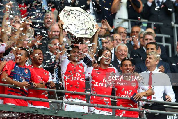Mikel Arteta of Arsenal holds up the trophy watched by Arsene Wenger manager of Arsenal after the FA Community Shield match between Manchester City...