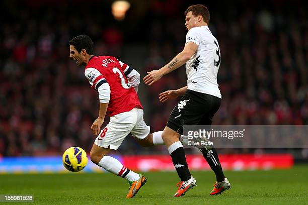 Mikel Arteta of Arsenal is challened by John Arne Riise of Fulham during the Barclays Premier League match between Arsenal and Fulham at Emirates...