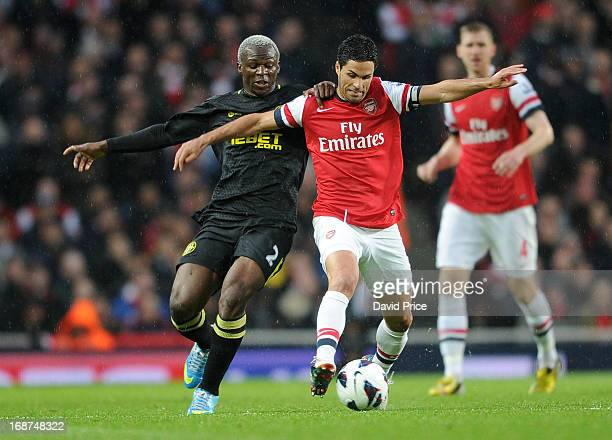 Mikel Arteta of Arsenal is pulled back by Arouna Kone of Wigan during the Barclays Premier League match between Arsenal and Everton at Emirates...