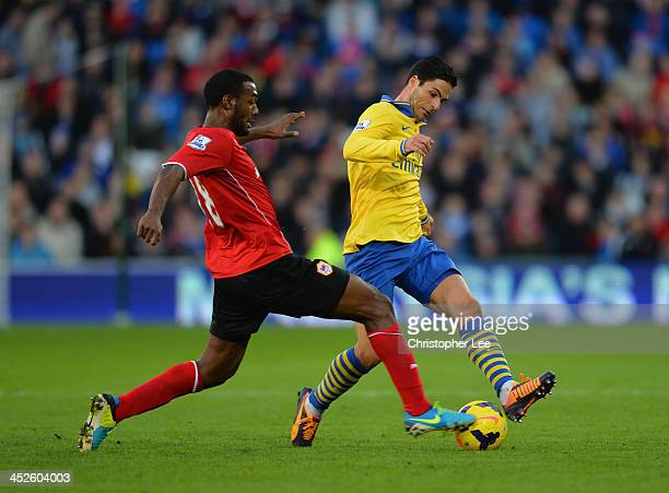 Mikel Arteta of Arsenal is tackled by Kevin TheophileCatherine of Cardiff during the Barclays Premier League match between Cardiff City and Arsenal...