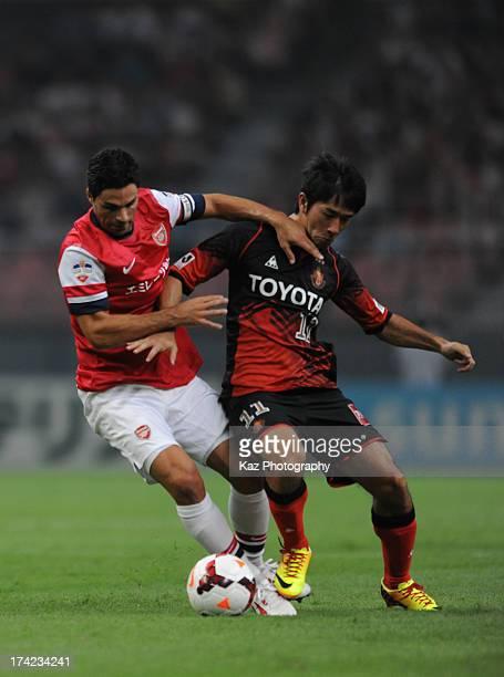 Mikel Arteta of Arsenal keeps the ball under the pressure from Keiji Tamada of Nagoya Grampus during the pre-season friendly match between Nagoya...