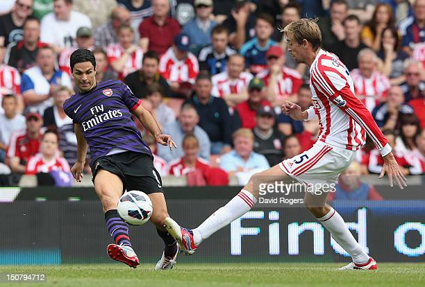 Mikel Arteta of Arsenal passes the ball past Peter Crouch during the Barclays Premier League match between Stoke City and Arsenal at the Britannia...