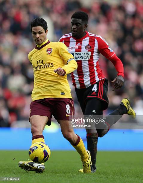 Mikel Arteta of Arsenal passes the ball whilst under pressure from Alfred N'Diaye of Sunderland during the Barclays Premier League match between...