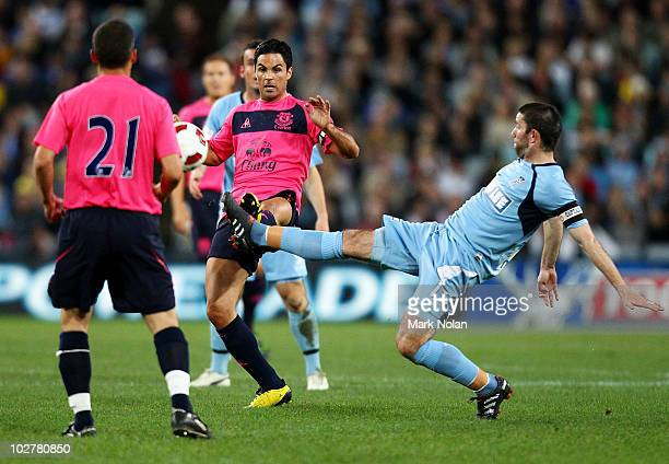 Mikel Arteta of Everton is tackled by Terry McFlynn of Sydney during a preseason friendly match between Sydney FC and Everton FC at ANZ Stadium on...