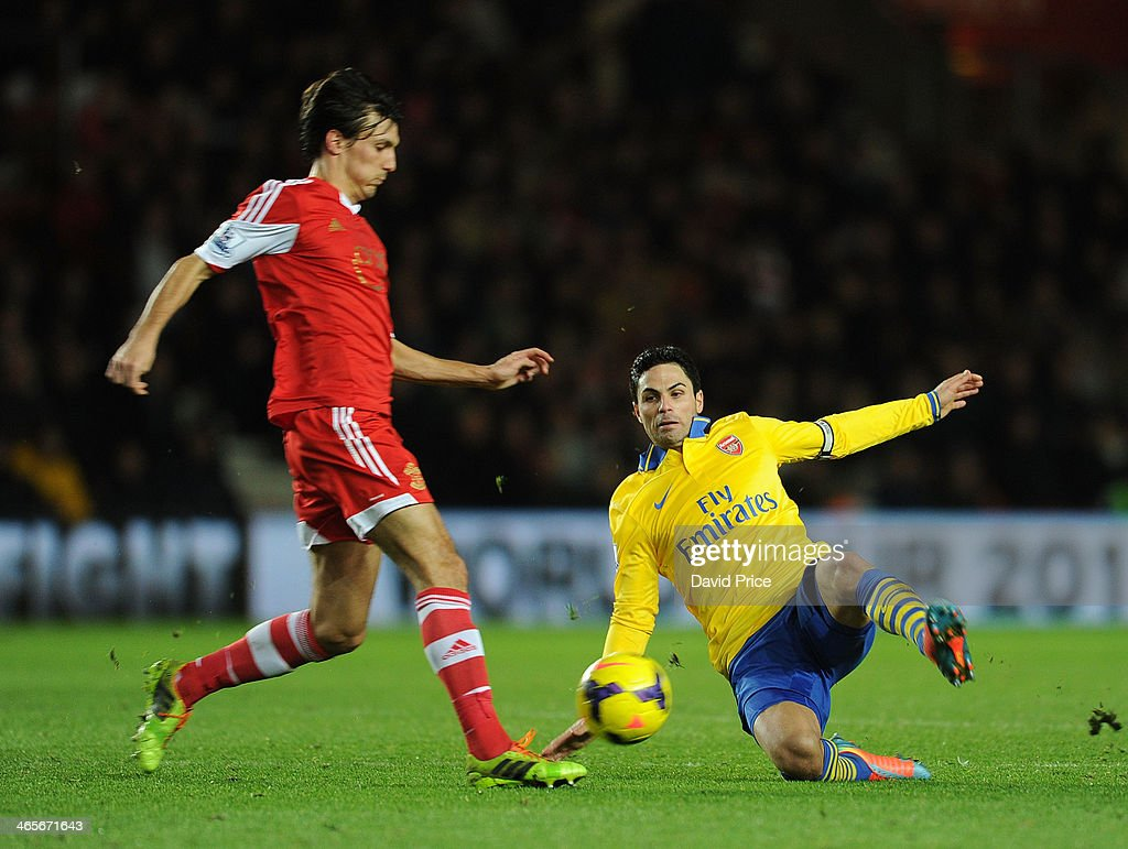 Mikel Arteta tackles Jack Cork of Southampton during the match between Southampton and Arsenal at St Mary's Stadium on January 28, 2014 in Southampton, England.