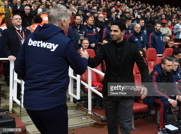 Mikel Arteta the Arsenal Head Coach shakes hands with David Moyes the West Ham Manager before the Premier League match between Arsenal FC and West...