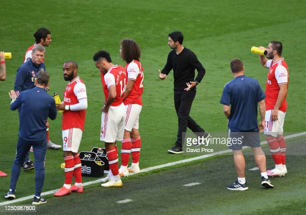 Mikel Arteta the Arsenal Head Coach talks to Dani Ceballos of Arsenal during the drinks break during the Premier League match between Brighton Hove...