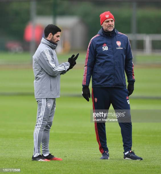 Mikel Arteta the Arsenal Head Coach talks to Steve Bould the Arsenal U23 Manager during a training session at London Colney on February 19 2020 in St...