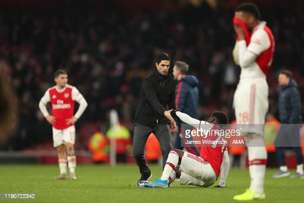 Mikel Arteta the manager / head coach of Arsenal helps up a dejected Bukayo Saka of Arsenal at full time of the Premier League match between Arsenal...