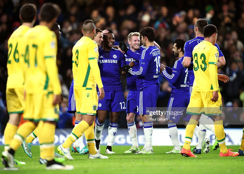 Mikel John Obi #12 of Chelsea is congratulated by teammates after scoring his team's third goal during the UEFA Champions League group G match between Chelsea and Sporting Clube de Portugal at Stamford Bridge on December 10, 2014 in London, United Kingdom.