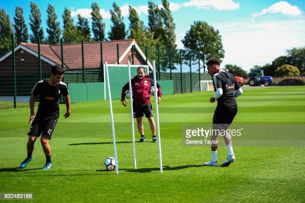Mikel Merino and Jacob Murphy pass the ball between training sticks under the watchful eye of Newcastle United's Head of Analysis and First Team...