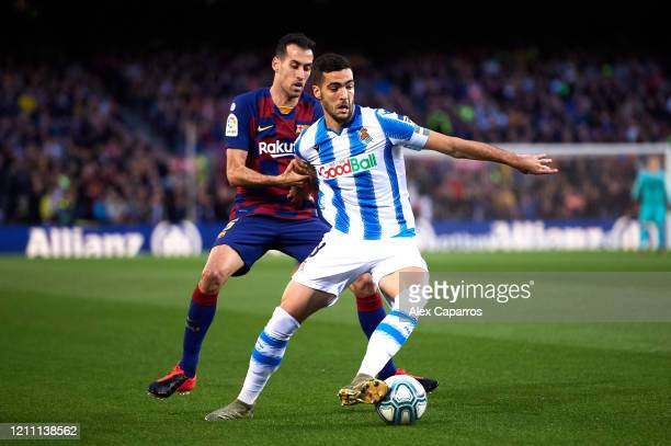 Mikel Merino of Real Sociedad controls the ball under pressure from Sergio Busquets of FC Barcelona during the Liga match between FC Barcelona and...