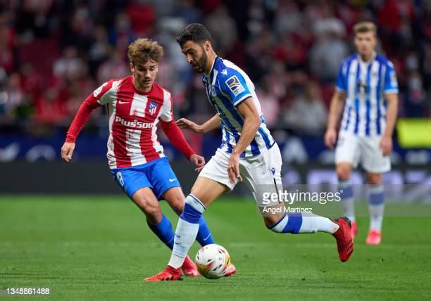 Mikel Merino of Real Sociedad is challenged by Antoine Griezmann of Atletico de Madrid during the LaLiga Santander match between Club Atletico de...