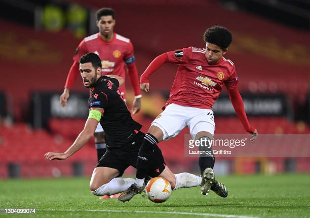 Mikel Merino of Real Sociedad is tackled by Shola Shoretire of Manchester United during the UEFA Europa League Round of 32 match between Manchester...