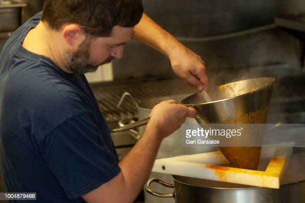 Mikel one of the cooks of the the Restaurante Hermandad de Pescadores strains the fish soup on July 24 2018 in Hondarribia Spain The restaurant...