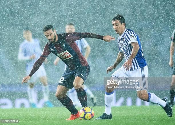 Mikel Oyarzabal of Real Sociedad competes for the ball with David Lomban of SD Eibar during the La Liga match between Real Sociedad and Eibar at...