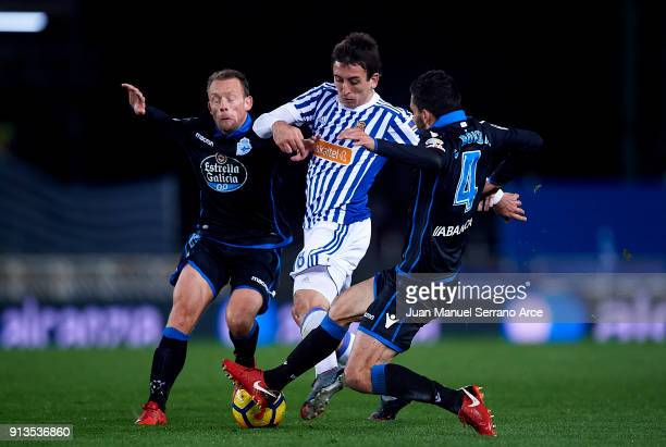 Mikel Oyarzabal of Real Sociedad duels for the ball with Michael KrohnDehli and Eneko Boveda of RC Deportivo La Coruna during the La Liga match...
