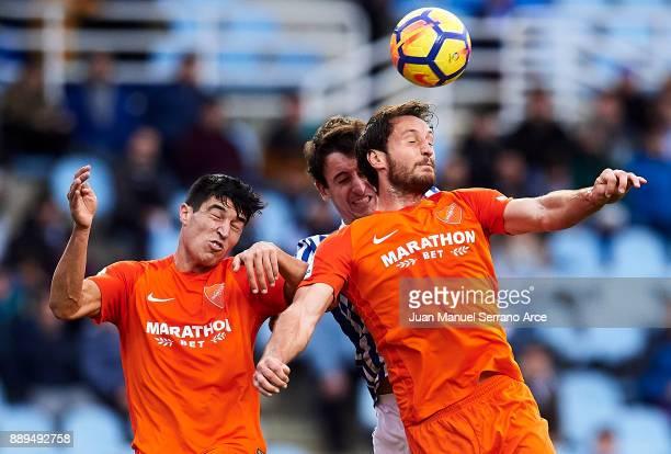 Mikel Oyarzabal of Real Sociedad duels for the ball with Paul Baysse of Malaga CF during the La Liga match between Real Sociedad de Futbol and Real...