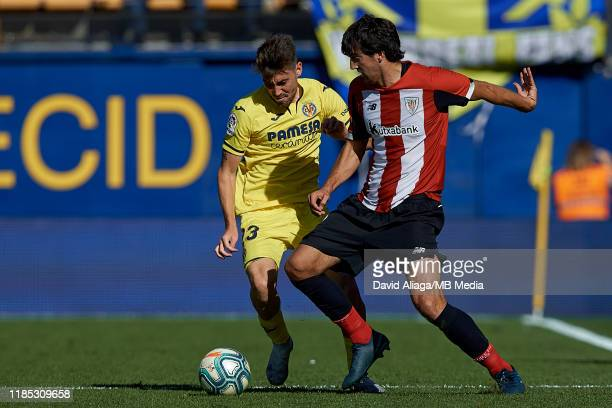 Mikel San Jose Dominguez of Athletic Club de Bilbao competes for the ball with Moi Gomez of Villarreal CF during the Liga match between Villarreal CF...