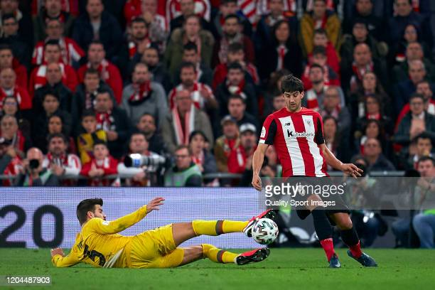 Mikel San Jose of Athletic Bilbao competes for the ball with Gerard Pique of FC Barcelona during the Copa del Rey Quarter Final match between...