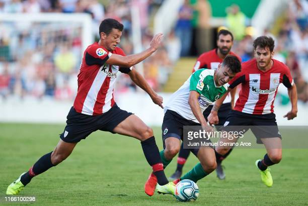 Mikel Vesga of Athletic Club duels for the ball with Aitor Bunuel of Real Racing Santander during the Pre-season friendly match between Real Racing...