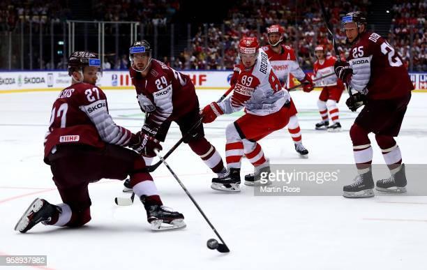 Mikelis Redlihs of Latvia and Mikkel Boedker of Denmark battle for the puck during the 2018 IIHF Ice Hockey World Championship Group B game between...
