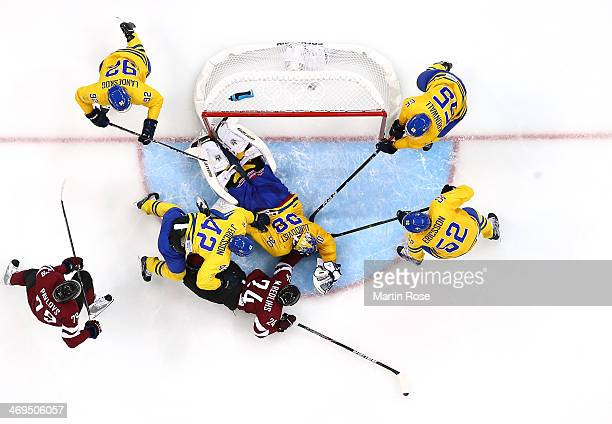 Mikelis Redlihs of Latvia falls to the ice while trying to score against Jimmie Ericsson and Henrik Lundqvist of Sweden in the second period during...