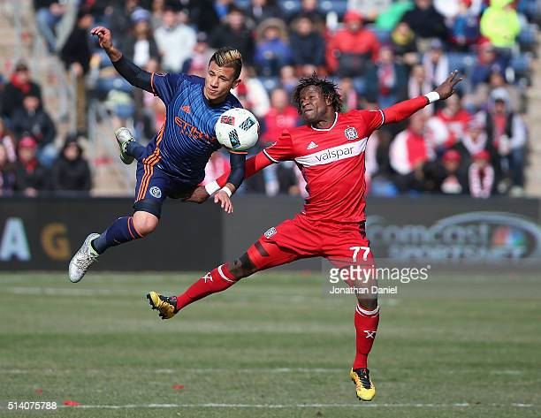 Mikey Lopez of the New York City FC and Kennedy Igboananike of Chicago Fire go airborne as they battle for the ball at Toyota Park on March 6 2016 in...