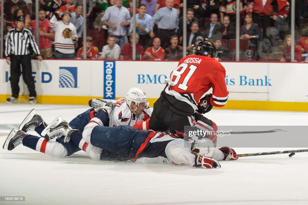 Mikhail Grabovski #84 and Mike Green #52 of the Washington Capitals slide into Marian Hossa #81 of the Chicago Blackhawks as he takes the puck toward an empty net in the end of the third period, during the NHL game on October 1, 2013 at the United Center in Chicago, Illinois.