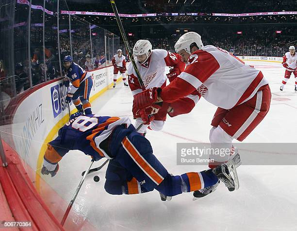 Mikhail Grabovski of the New York Islanders is checked by Jonathan Ericsson of the Detroit Red Wings during the second period at the Barclays Center...