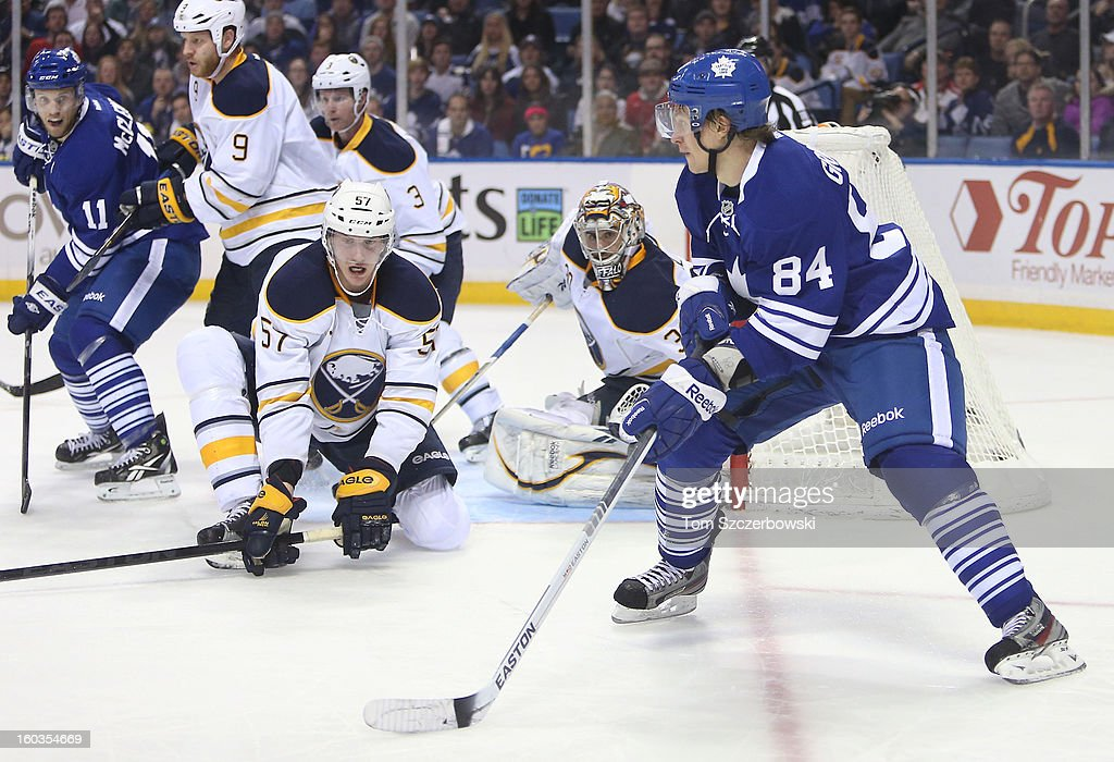 Mikhail Grabovski #84 of the Toronto Maple Leafs comes in front of the net with the puck during their NHL game as Tyler Myers #57 and Ryan Miller #30 of the Buffalo Sabres defend at First Niagara Center on January 29, 2013 in Buffalo, New York.