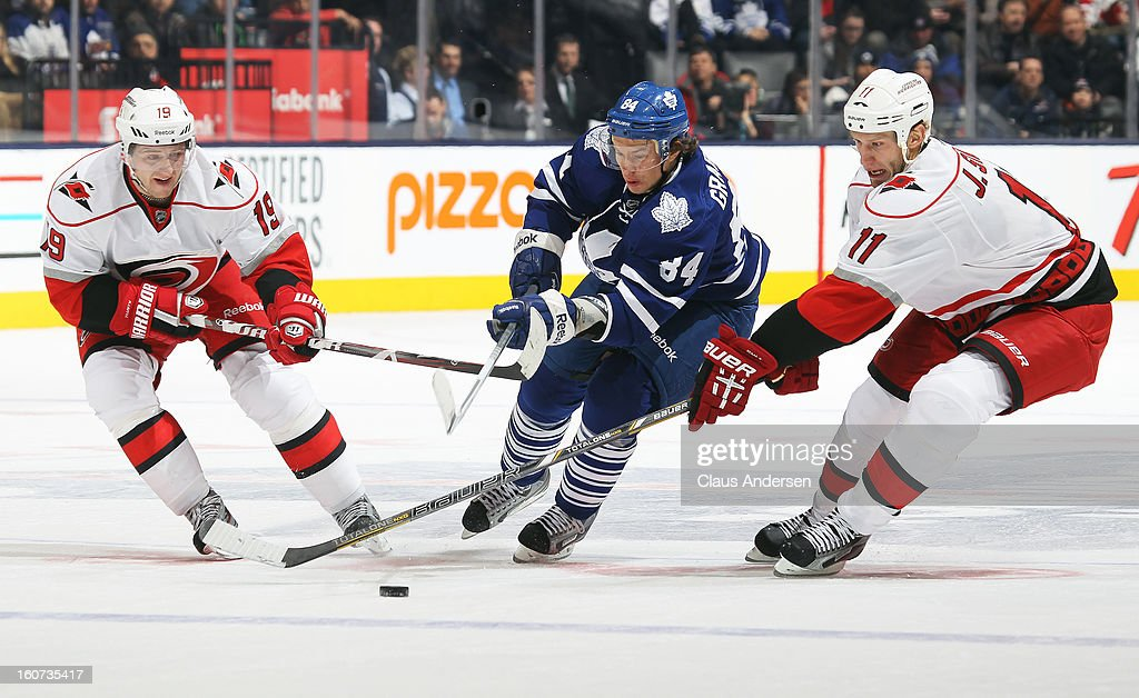 Mikhail Grabovski #84 of the Toronto Maple Leafs tries to split between Jiri Tlusty #19 and Jordan Staal #11 of the Carolina Hurricanes in a game on February 4, 2013 at the Air Canada Centre in Toronto, Canada. The Hurricanes defeated the Leafs 4-1.
