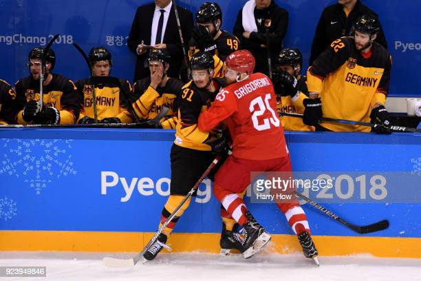 Mikhail Grigorenko of Olympic Athlete from Russia collides with Moritz Muller of Germany in the first period during the Men's Gold Medal Game on day...